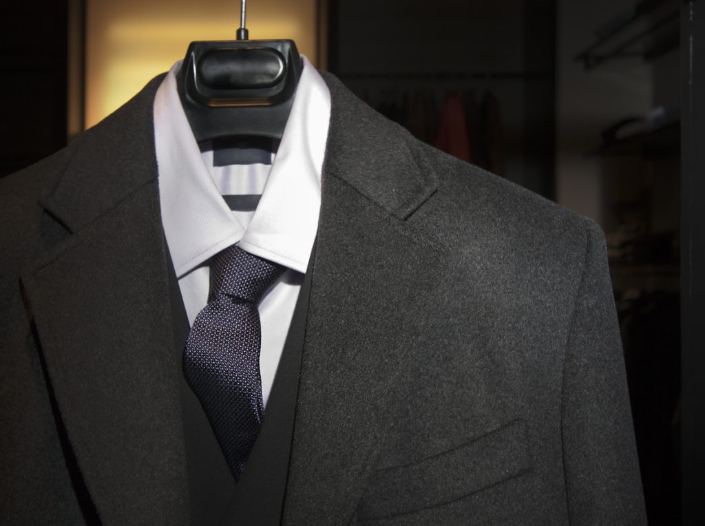 Suit, vest, shirt and necktie on a hanger.